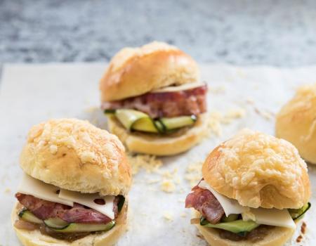 Pan brioche stile hamburger, zucchine marinate, porzione di Entremont Emmental e petto di pollo grigliato